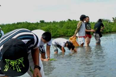 (standing second from right): James Castillo, foundation board member, leads youth participants in planting mangrove trees in Cebu, Philippines