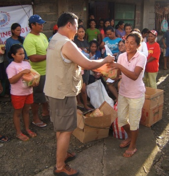 Dale Asis, Bayanihan Foundation Worldwide handing out emergency food supplies in Giporlos, Samar November 2014