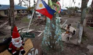 Children in Tanauan, in the Philippines' Leyte province, play beside an improvised Christmas tree decorated with cans and bottles. (Image: Romeo Ranoco, Reuters)