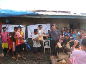 (center, stripe shirt) Arman Mulleem of Worldwide Filipino Alliance distributing relief goods