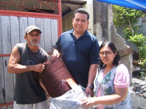 (left to right): (standing left) fisherman receiving fishing net provided as a microloan from Dale Asis (center) and Evelyn Castillo (standing right)