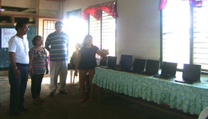 (standing left to right) Dale Asis and Evelyn Castillo handing over six laptop computers to the Giporlos Central Elementary School