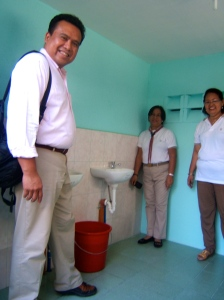 (standing left) Dale Asis inspecting new wash basins with running water, with Principal Vivian Santiago and teacher Ms. Gutierrez looking on