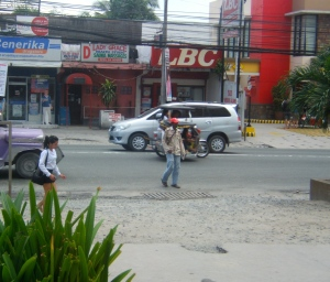 Filipino Amerasian (center wearing red cap) helping parked cars for tips as a means to earn a living (2014)