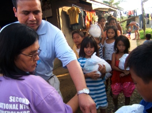 Evelyn Castillo and Dale Asis distributing food to street children in Tacloban City, Leyte Philippines (2014)
