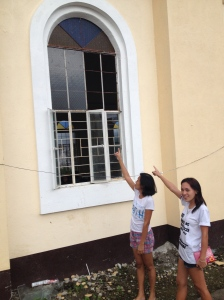 Volunteers Roxzine Albutra and Gretchen Lo points out the broken stained glass windows of historic Giporlos Church being replaced