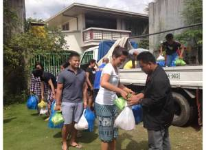 (left to right): Marc Butiong and Crystle Dino distributing food packages to indigent Filipino Muslims