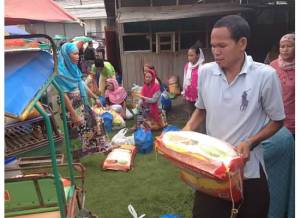 Man receiving sack of rice as part of Ramadan gift giving