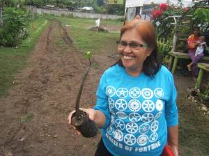Evelyn Castillo, Bayanihan Foundation liaison holding up a mangrove tree seedling in Liloan, Cebu