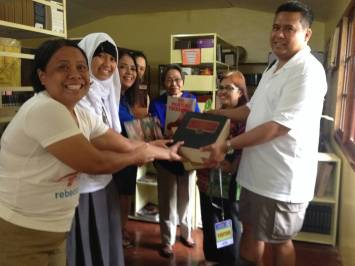 (standing far left) Iligan Central Elementary School librarian Idamarie Navarro symbolically receives the donated books from Evelyn Castillo (second to the right) and Dale Asis (standing far right)