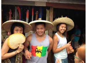Marc Butiong (center) tries out a traditional sombrero with Stephanie Camba (left) and Crystle Dino (right)