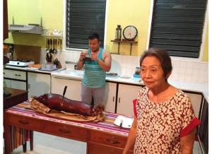 Marc Butiong (center) takes a photo of the lechon with host Mrs. Luz Saavedra (standing right)