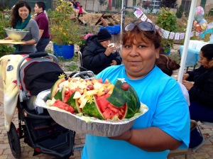 Community resident of Chicago's Little Village neighborhood carved out a boat of fruit for the community dinner celebration